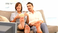 Young couple watching tv with popcorn video