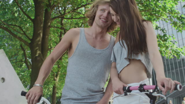 Young couple with bicycles in a modern city video