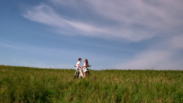 Young couple with bicycles in the green field video
