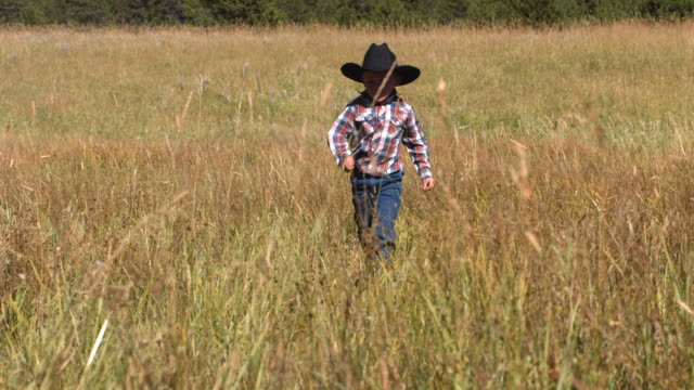 Young cowboy runs in grassy field, slow motion video
