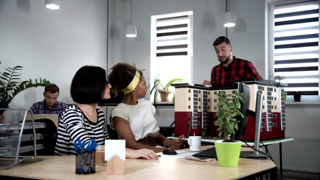 Young coworkers communicating in office video