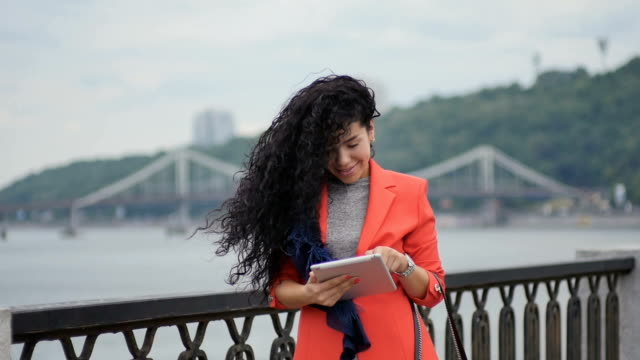 Young curly brunette uses tablet at bridge background video