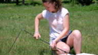 Young curly girl pitches a tent in the park video