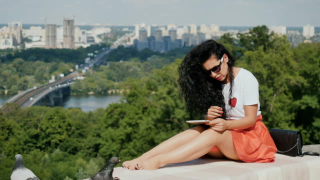 Young curly girl relax on plaid with tablet against modern city video