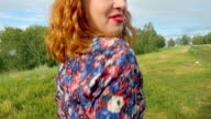Young curly red-haired woman dancing and singing happy in summer meadow video