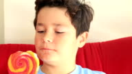 Young cute boy with big colorful lollipop candy video
