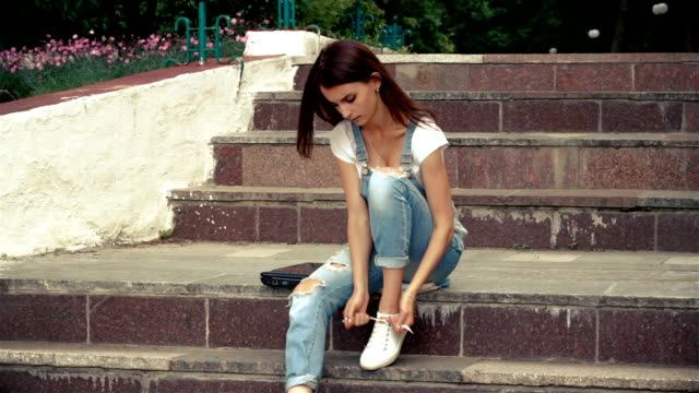 young cute brunette sits on the steps and ties shoelaces video