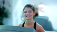 Young cute girl running in the gym smiling and looking at the camera video