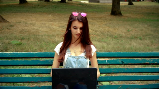 young cute women sitting on a bench and looking at laptop video