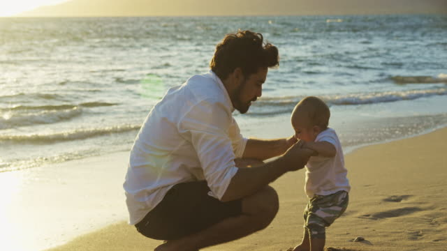 Young dad holding baby boy at sunset in slow motion video
