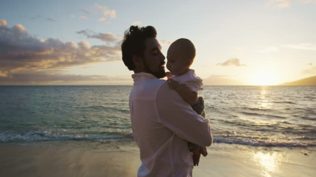 Young dad holding up baby at sunset in slow motion video