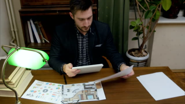 Young designer holding tablet pc and checking business papers on his table video