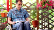 Young disabled man reading book video