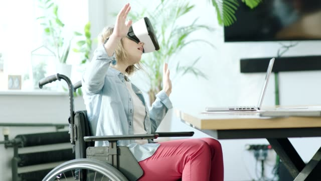 Young disabled woman using virtual reality headset video