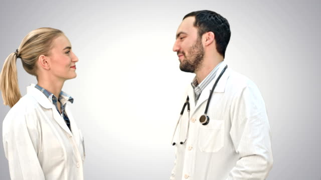 Young doctor joking on his collegue not give five on white background video