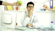Young Doctor Thinking Healthy Apple or Pills Offering Fruit video