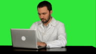 Young doctor thinking idea with laptop computer on the table on a Green Screen, Chroma Key video