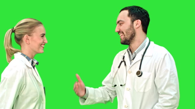 Young doctors give each other five and smiling on a Green Screen, Chroma Key video