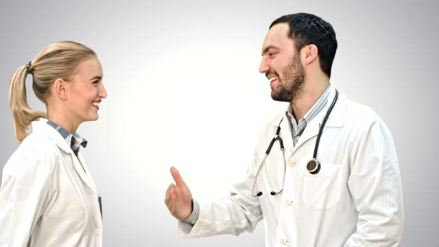 Young doctors give each other five and smiling on white background video