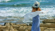 Young elegant woman holding scarf in wind, ocean waves crashing video