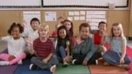 Young elementary school class sit waving to camera video