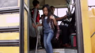 Young elementary school kids getting off a school bus video