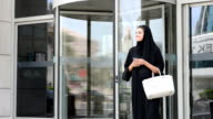 Young Emirati woman by the revolving door video