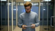 Young employee walks with digital tablet video