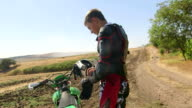 Young enduro racer dressing motorcycle protective gear beside his dirt bike video