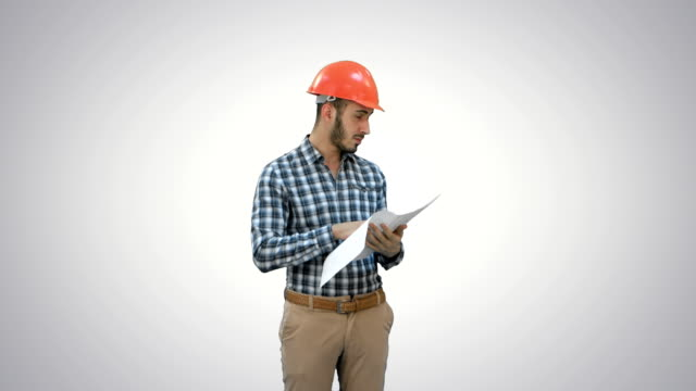 Young engineer in helmet checking construction plan on white background video