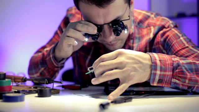 Young engineer looks at the printed circuit board in different glasses. video