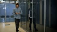 Young entrepreneur walks in corridor with tablet smart phone video