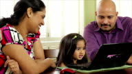 Young ethnic family with daughter on laptop video