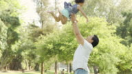 Young ethnic father playing with his baby girl throwing her in the air video
