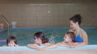 Young ethnic swimming instructor working with children in pool video