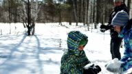 Young family are playing in snowballs in nature in winer video