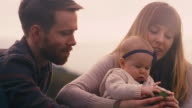 A young family at a picnic eating vegetables on a fall day, slow motion video