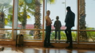 Young family in airport terminal. Stand at the window, look at the planes. Outside, a sunny day, palm trees grow. Arriving at a tropical resort video