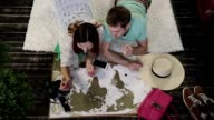 Young family marking places to visit on travel map video