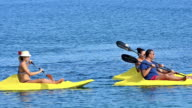 Young family people having fun at sea kayaking video
