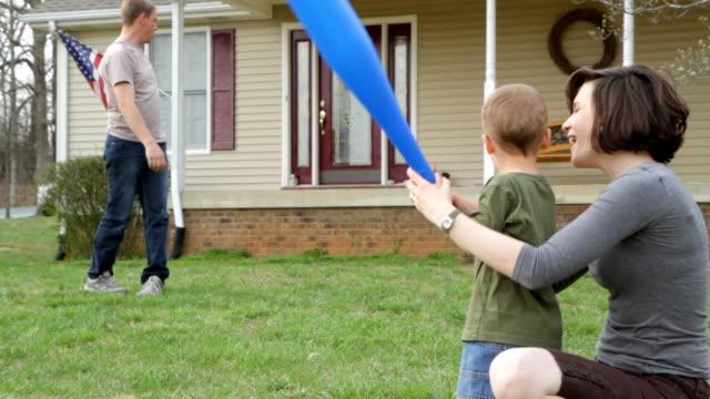 Young family play baseball video