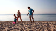 Young family playing football on the beach video