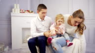 Young family plays with their baby girl at home at fire place video