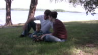 Young family sits at edge of lake HD video
