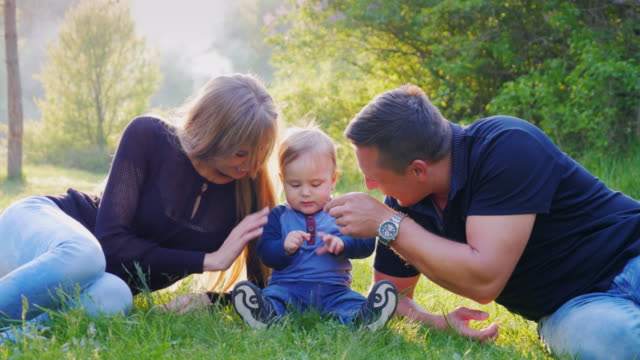 A young family with a child is resting in the park. Play with your baby boy, 1 year old video