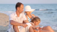 Young family with little daughter sitting in evening on sand beach video