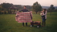 A young father lays out a blanket for a picnic while his wife holds their baby, on a fall day video