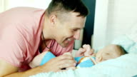 Young father smiling happily to his baby. He looks at it, close-up video