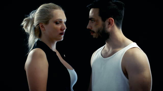 Young Female and Man with a Bruised Faces Look Aggressively at Each Other and Then into the Camera. Possible Domestic Dispute/ Conflict Theme. Background is Isolated Black, video