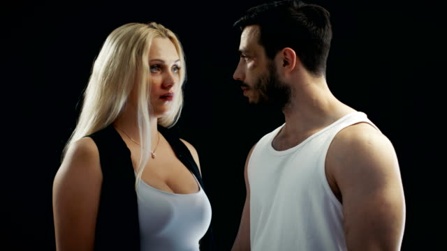 Young Female and Man with a Bruised Faces Touchingly Looking at Each Other and Then into the Camera. Possible Domestic Violence Theme. Background is Isolated Black, video